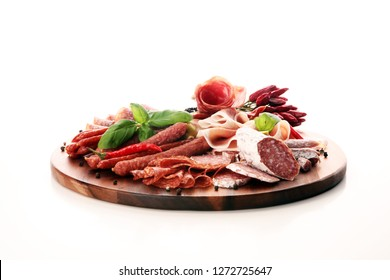 Food tray with delicious salami, pieces of sliced prosciutto crudo, sausage and basil. Meat platter with selection.
