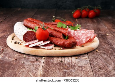 Food tray with delicious salami, sausage, tomatoes, salad. Meat platter with selection. Cutting sausage
