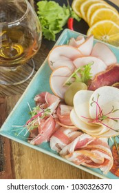 Food tray with salami,sausage, dried meat, slices of chopped ham, with lemon, microgreen salad and vegetables in a blue plate, meat dish with a choice. Wooden background.Glass, cognac