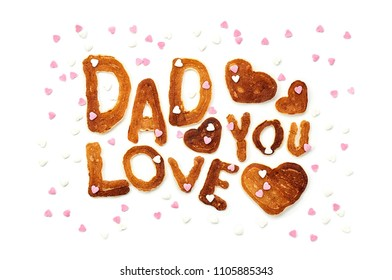 Food typography phrase Dad Love You performed from Alphabet Pancakes with sprinkles. Lettering Isolated on white background. Top view, close up