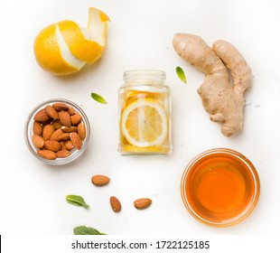 Food useful for immunity. Lemon in honey-sugar syrup with ginger and mint in a jar on a white background
