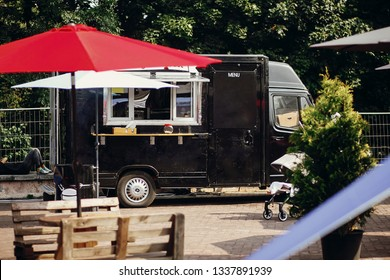 Food van truck. Stylish black mobile food truck with burgers and asian food at street food festival. Summer eating market in the city. Space for text, menu