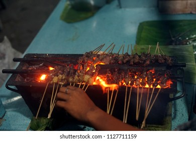 Food Vendor Grilling Meat Satay with charcoal at Street Food Market