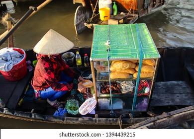 A food vendor selling banh mi on a sampan (wooden boats) at Cai rang Floating Market in Can tho, Vietnam
