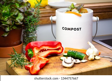 Food waste recycle, real kitchen food waste from food preparation collected for recycling in kitchen compost collecting pot container with chopped vegetables on chopping board