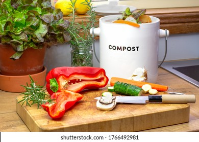 Food waste recycling in kitchen, food waste from food preparation collected for recycling in kitchen compost collecting pot container with chopped vegetables with knife on chopping board