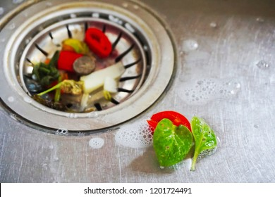 Food waste from the washing up in the sink and trash traps grid of drainage holes.