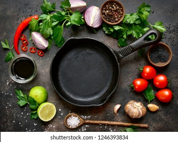 Food,background with empty frying pan and ingredients for cooking on a dark slate, stone or concrete backdrop.Top view with copy space.