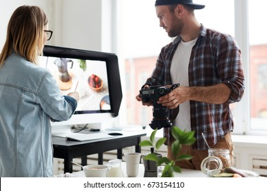 Food-bloggers discussing one of shots in computer monitor