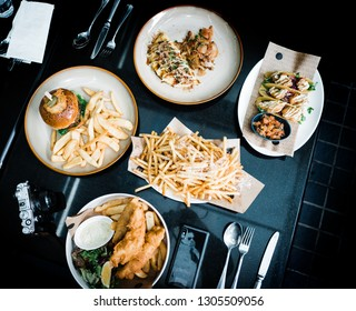 foodgram of cheeseburger, french fries, taco, fish and chips and ommelete on a black table