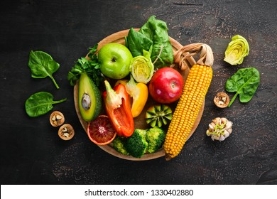 Foods containing natural fiber: avocados, kiwi, apple, tomatoes, spinach, paprika, orange, lemon. Top view. Free space for your text. On a brown background.