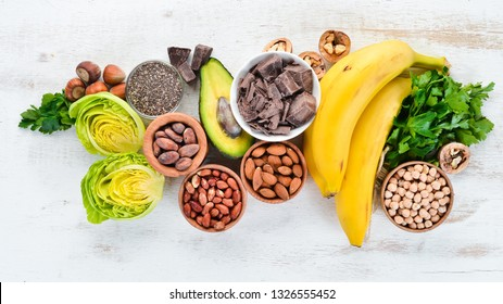 Foods containing natural magnesium. Mg: Chocolate, banana, cocoa, nuts, avocados, broccoli, almonds. Top view. On a white wooden background.