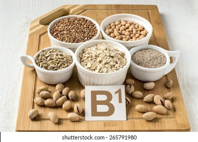 Foods containing vitamin B1: oatmeal, buckwheat, bran, peas, sunflower seeds, pistachios in a cup on a wooden board