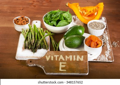 Foods containing vitamin E on a wooden board. View from above
