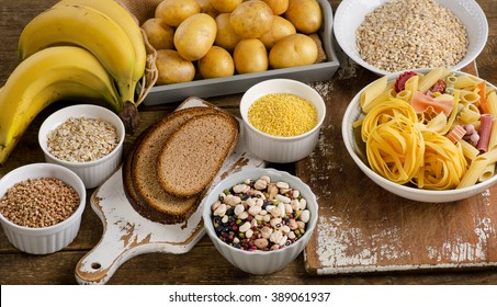 Foods high in carbohydrate on a rustic wooden table. Top view