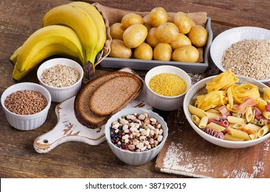 Foods high in carbohydrate on wooden table. Top view
