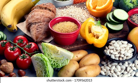 Foods high in carbohydrates on grey background. Vegan Foods high in dietary fiber, antioxidants, vitamins and minerals.