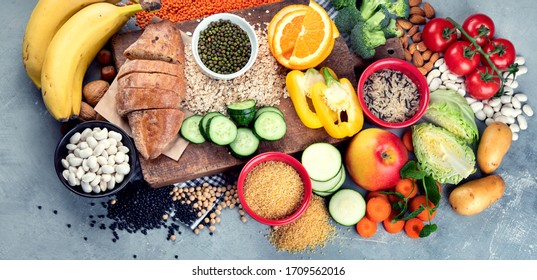 Foods high in carbohydrates on grey background. Vegan Foods high in dietary fiber, antioxidants, vitamins and minerals. Top view. Panorama, banner