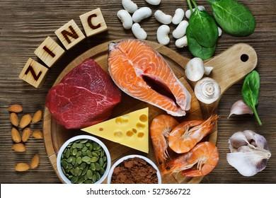 Alimentos Altos en zinc como salmón, gambas, carne de res, queso amarillo, espinacas, hongos, cacao, semillas de calabaza, ajo, judías y almendras. Vista superior