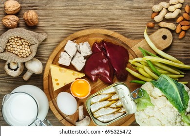 Foods rich in Biotin (vitamin B7). Foods as liver, eggs yolk, yeast, cheese, sardines, soybeans, milk, cauliflower, green beans, mushrooms, peanuts, walnuts and almonds on wooden table