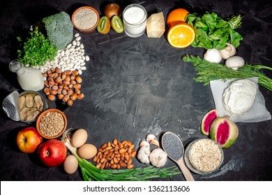 Foods rich in calcium such as sardines, bean, dried figs, almonds, cottage cheese, hazelnuts, parsley leaves, broccoli, italian cabbage, cheese on dark background