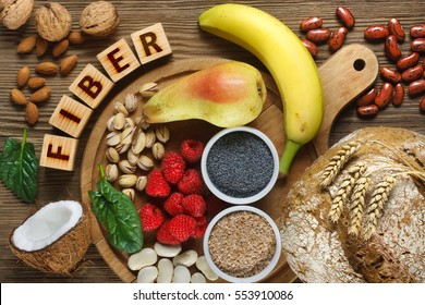Foods rich in fiber as rye bread, wheat bran, white beans, red beans, spinach, almonds, poppy seed, pears, bananas, coconut, raspberries, pistachios, walnuts. Wooden table as background