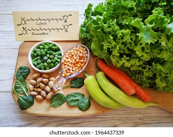 Foods rich in lutein and zeaxanthin with structural chemical formulas of two carotenoids. Fresh vegetable as best food sources of lutein and zeaxanthin. Spinach, carrot, peas, corn, pepper, lettuce.