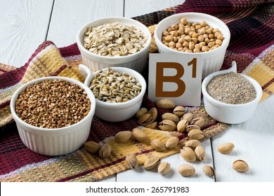 Foods rich in vitamin B1: buckwheat, oatmeal, bran, sunflower seeds, peas, pistachio nuts in a cup on a brown napkin