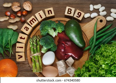 Foods rich in vitamin B9 (folic acid) as liver, asparagus, broccoli, eggs, salad, avocado, yeast, nuts, spinach, orange and beans. Top view