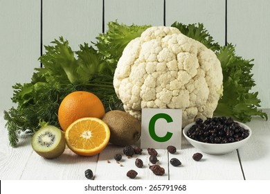 Foods rich in vitamin C: currants, dried rose hips, cauliflower, lettuce, dill, orange, kiwi on a light background