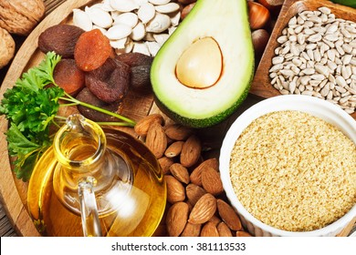 Foods rich in vitamin E such as wheat germ oil, dried wheat germ, dried apricots, hazelnuts, almonds, parsley leaves, avocado, walnuts, pumpkin seeds, sunflower seeds on wooden table