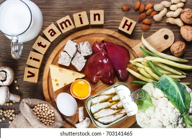 Foods rich in vitamin H (Biotin). Foods as liver, eggs yolk, yeast, cheese, sardines, soybeans, milk, cauliflower, green beans, mushrooms, peanuts, walnuts and almonds on wooden table