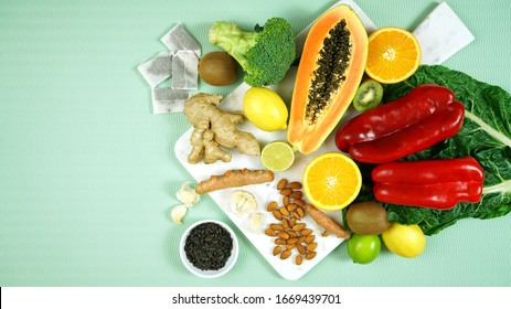 Foods that boost the Immune System. Citrus, red bell peppers, broccoli, garlic, ginger, spinach, almonds, turmeric, green tea, papaya, kiwi fruit, poultry and sunflower seeds. Negative copy space.
