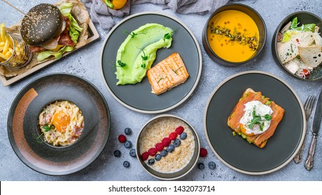 Foodset on table. poached egg with salmon and avocado on a white plate, burger, grilled salmon with mashed beens, pumpkin soup, carbonara and oatmeal porridge top view food.