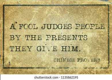 A fool judges people by the presents they give him - ancient Chinese proverb printed on grunge vintage cardboard