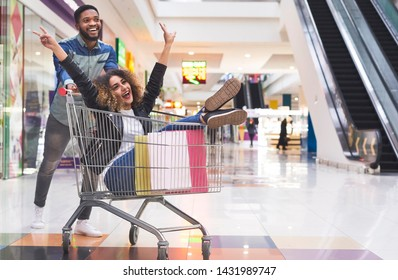 Foolling together. Young african couple having fun while shopping, man pushing shopping cart with girl inside, panorama