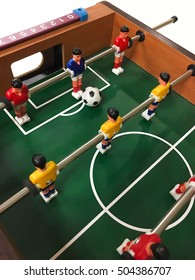 Foos ball table with soccer ball.