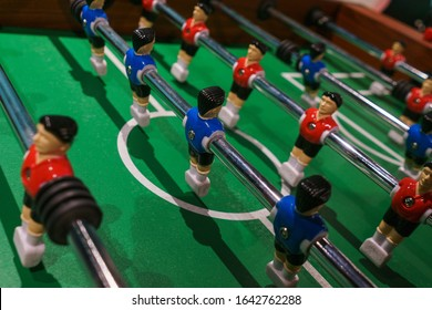 Foosball, miniature plastic players of blue and red teams against each other. Entertainment and games. Competition and challenge. Results and goal, concept. Vintage toning.