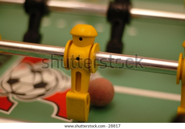 """A foosball """"player"""" gets ready to kick the ball."""