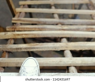 The foot is about to step down from a temporary wooden staircase in a building under construction.