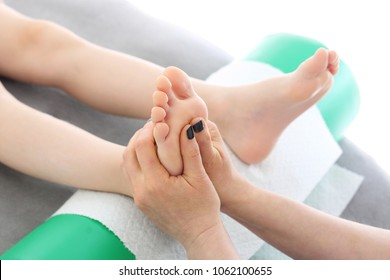 Foot acupressure. The masseur performs a point massage of the child's foot
