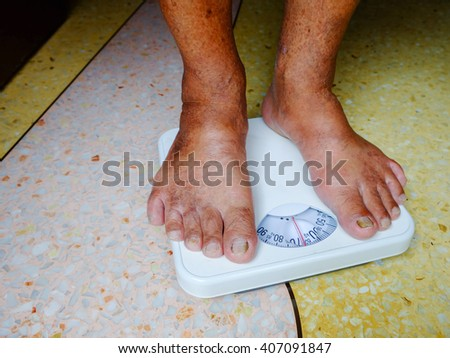 Foot Of Aged Man Standing On Weight Scale