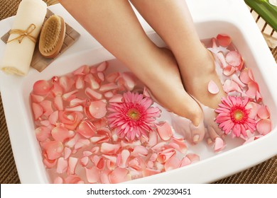 Foot bath in bowl with flower petals