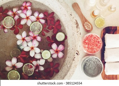 Foot bath in bowl with lime and tropical flowers, spa pedicure treatment, top view
