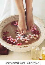 Foot bath in bowl with tropical flowers and oil, spa pedicure treatment