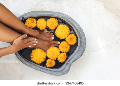 Foot bath in stone basin with tropical flowers, spa pedicure treatment, top view