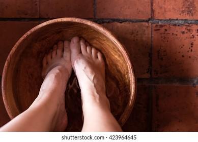 foot bath in a wooden bowl preparing for reflexology