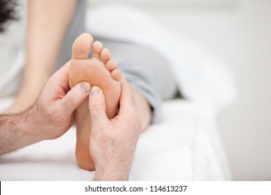 Foot being massaged on a medical table in a room