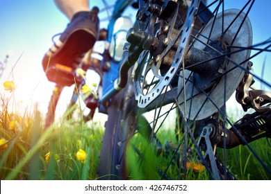 Foot of bicyclist on the pedal in the grass. Close up of the brakes.
