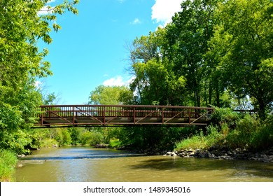 A foot bridge crossing Root River in Lincoln Park in Racine Wisconsin on a sunny summer afternoon.  The river flows under the bridge into the distance.  A few clouds highlight the blue sky.